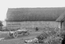 A new wagon next to a barn