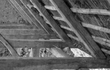 A rafters setting on beams in an old brick barn